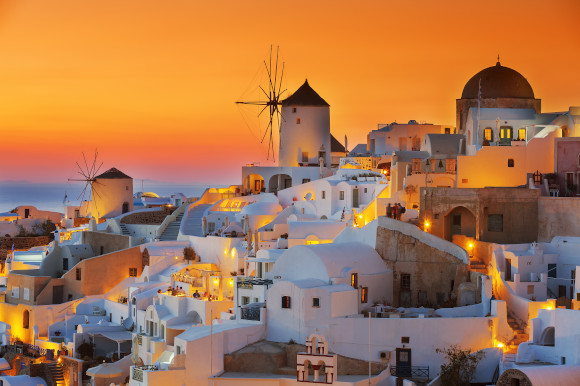 Santorini's famous sunset showing whitewashed buildings and a bright orange sky
