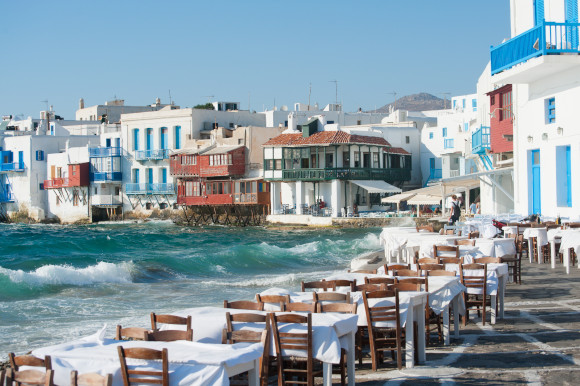 Little Venice in Mykonos with restaurants lining the water's edge and houses sitting over the water