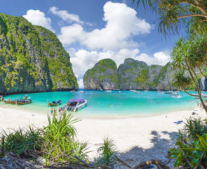 The famous Maya Bay in Thailand's popular Phi Phi Islands with long tail boats in the water and striking white sand