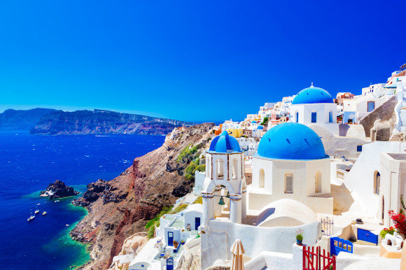 Sun-soaked views over the Iconic Oia in Santorini featuring whitewashed buildings and blue-domed churches