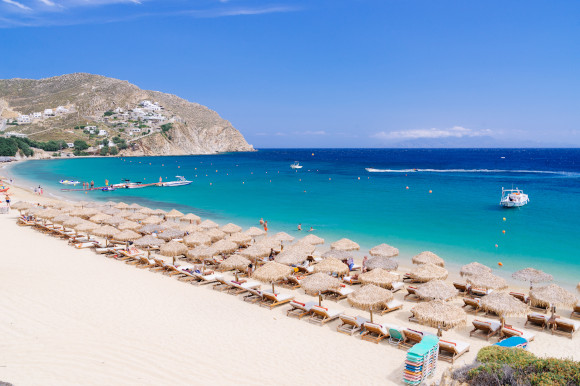 The busy Paradise Beach on the Greek Island of Mykonos filled with sunloungers and blessed with white sand