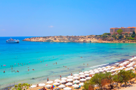 Coral Bay in Paphos, Cyprus with stunning waters and white umbrellas lining the sand
