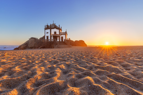 The striking Praia de Miramar in Portugal at sunset with rippled sands and a traditional chapel in the distance