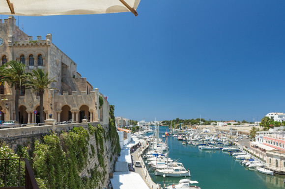 The stunning Town Hall overlooking Ciutadella port in Menorca with yachts sitting in the water