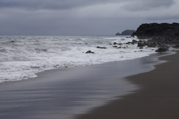 The volcanic, black sands of Praia de Santa Barbara Beach in the Azores region of Portugal