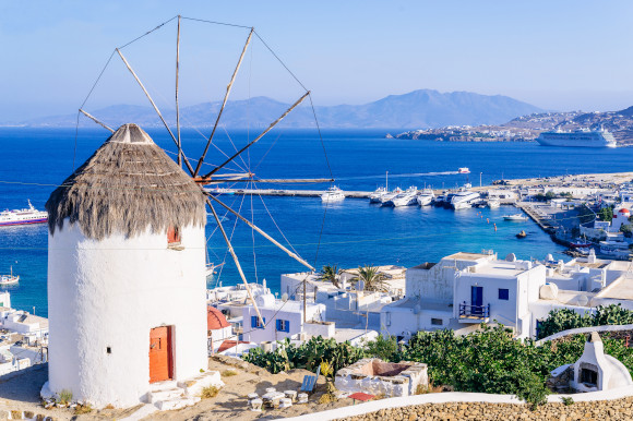 An elevated view of the iconic windmills on the Greek Island of Mykonos with the Aegean Sea in the distance