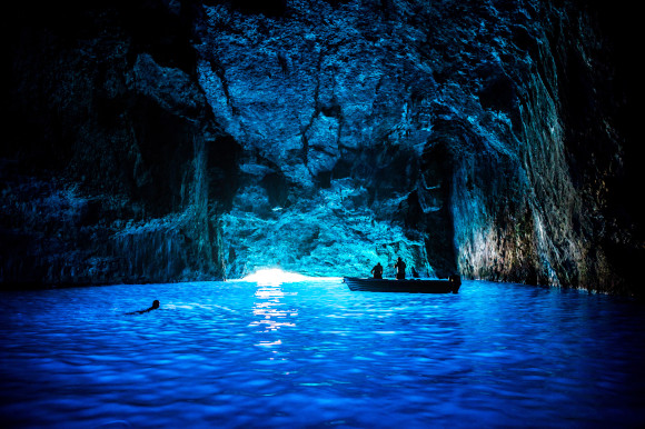The dark caves of Kas featuring a small fishing boat and diver exploring