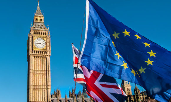 European and UK flag in front of Big Ben with a bright blue sky as the backdrop