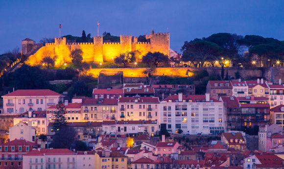 Lisbon's skyline at night with a lit-up castle perched high up on the hillside