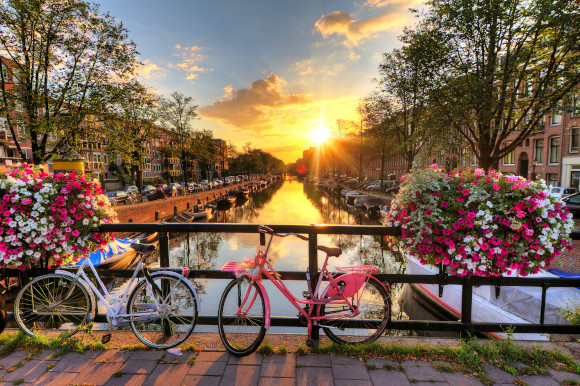Colourful bikes lying along the canal front in Amsterdam at sunrise