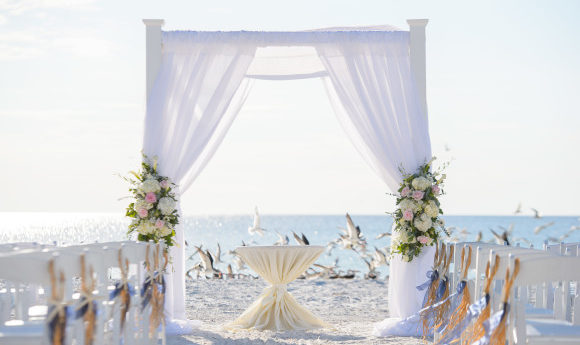 Beautiful white beach wedding on the shores of Spain with decorated white chairs and flowered walkway