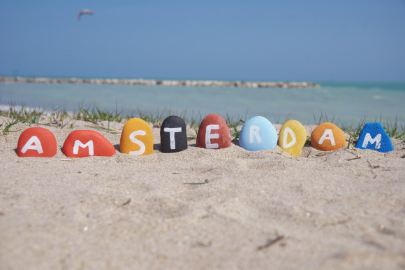 Painted rocks spelling Amsterdam on Blijerg aan Zee Beach Holland