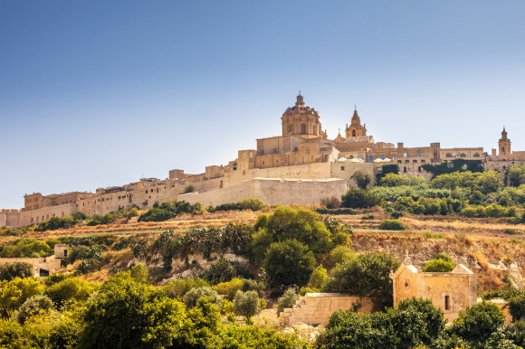 A view of the Mdina Old City and its medieval buildings against a blue sky backdrop