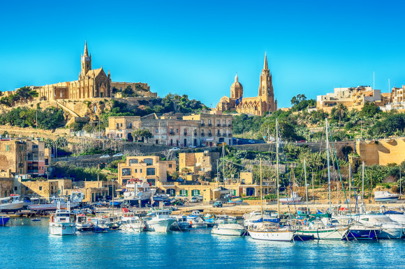 A sun-filled view of the Island of Gozo with yachts in the sitting in the water and beautiful buildings peering in the distance.