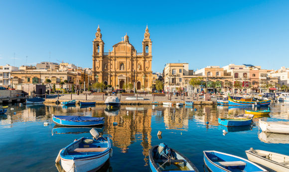 Malta Sliema town and its waterfront with floating boats and views of the dominating cathedral