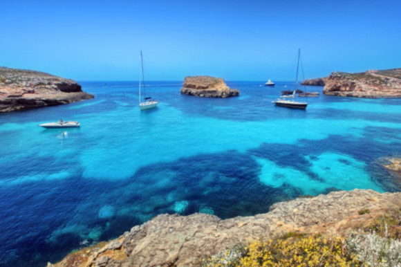 The Blue Lagoon and its yacht-filled waters and azure waters on the island of Comino Malta