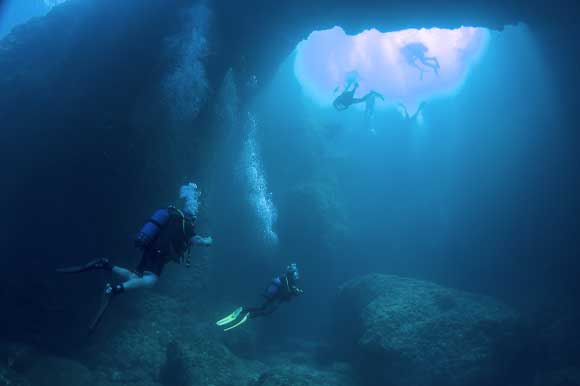 Shot of divers in the Blue Hole's underwater tunnel
