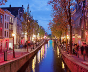 A beautiful view of Amsterdam at dusk showing a canal surrounded by grand buildings and trees