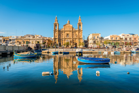 Views of the church in Sliema and the surrounding waters with floating fisherman boats in Malta