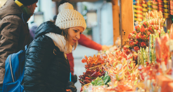 A woman shopping for gifts at a Christmas market