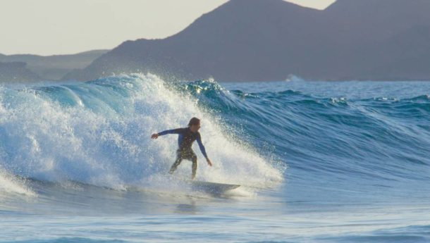 A surfer riding the big waves on a beach in Fuerteventura
