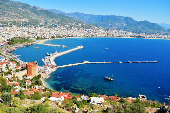 The beautiful Alanya harbor surrounded by azure waters and towering mountains