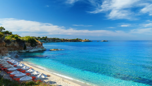 beach with white sand and clear blue water in a beautiful Bay with sun beds and umbrellas, Crete, Greece
