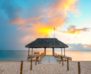 An amazing sunset in Mauritius with white sands surrounding a jetty and the sea sitting in the distance