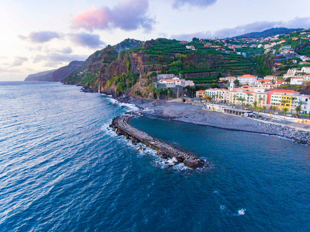 The sun setting below Madeira island with the Atlantic Ocean and orange roofed houses in the background