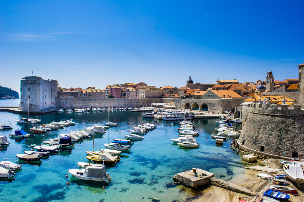 Port of Dubrovnik with a scattering of boats and the city walls in the backdrop