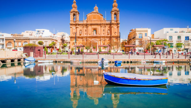 Valletta, Malta. Msida Marina boat and church reflection into water.