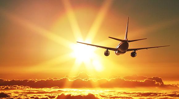 Plane flying towards beautiful sunset